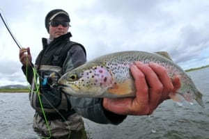 A proud angler shows why he hired an Alaska fishing charter by holding up a beautiful rainbow trout.